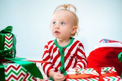Cute baby girl 1 year old near santa hat posing over Christmas background. Sitting on floor with Christmas ball. Holiday stock photography