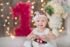 Cute baby girl 1-2 year old sitting on floor with pink balloons in room over white. Isolated. Birthday party. Celebration. Happy b Stock Image