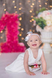 Cute baby girl 1-2 year old sitting on floor with pink balloons in room over white. Isolated. Birthday party. Celebration. Happy b Royalty Free Stock Images