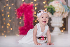 Cute baby girl 1-2 year old sitting on floor with pink balloons in room over white. Isolated. Birthday party. Celebration. Happy b Stock Images