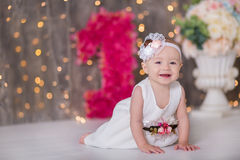 Cute baby girl 1-2 year old sitting on floor with pink balloons in room over white. Isolated. Birthday party. Celebration. Happy b Stock Photography