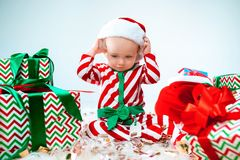 Cute baby girl 1 year old wearing santa hat posing over Christmas background. Sitting on floor with Christmas ball stock photo