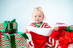 Cute baby girl 1 year old wearing santa hat posing over Christmas background. Sitting on floor with Christmas ball royalty free stock photos