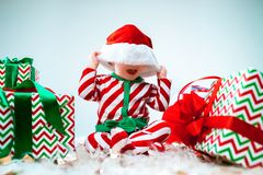 Cute baby girl 1 year old wearing santa hat posing over Christmas background. Sitting on floor with Christmas ball royalty free stock image