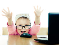 Cute baby with glasses looking into the laptop Stock Photos