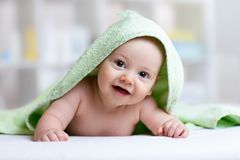 Cute baby in green towel after bathing stock photos