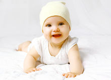 Cute baby in hat on the bed. Having fun Royalty Free Stock Image