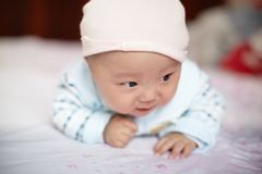 Cute baby in hat on the bed Stock Images