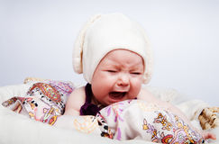 Cute baby in the hat crying out loud. Cute crying child dressed in a hat with ears lying on his tummy in a basket royalty free stock image
