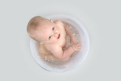 Cute baby having a bath in transparent bucket and playing. Little girl having a bath in the transparent bathing bucket and playing with  rubber turtle Stock Photos
