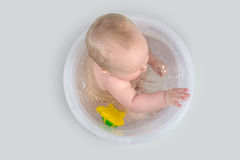 Cute baby having a bath in transparent bucket and playing with t Stock Photos
