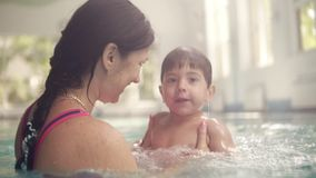 Cute baby having swimming lesson with his mother. Mother teaching her son to swim in the swimming pool. Young mom takes. Her son and embraces him. Indoors stock footage