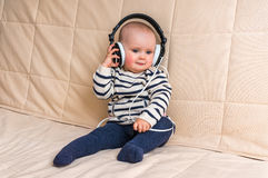 Cute baby with headphones listens to music at home Royalty Free Stock Image