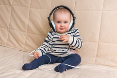 Cute baby with headphones listens to music at home Stock Photo