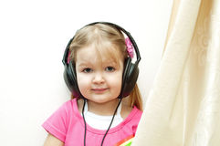 Cute baby with headphones. Little beautiful girl in headphones listens to music Stock Photography