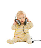 Cute baby in headphones sitting on floor Stock Photos