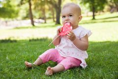 Cute baby with heart shaped lollipop at park Stock Images