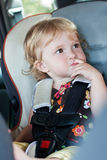 Cute baby his finger in his mouth. Sitting in the car seat royalty free stock photography