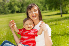 Cute baby and his mummy sitting in green meadow Stock Photos