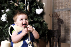 Cute baby hold the cone near xmas tree Royalty Free Stock Photo
