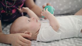 Cute baby holding blue toy. Newborn kid development. Lovely child study world. Cute baby holding blue toy. Close up of adorable child looking toy. Newborn kid stock footage