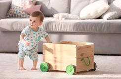 Free Cute Baby Holding On To Wooden Cart In Living Room Stock Image - 113600071