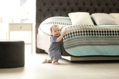 Cute baby holding on to bed at home stock image
