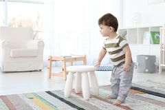 Cute baby holding on to stool at home. Learning to walk Stock Images