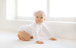 Cute baby at home crawls in white room Royalty Free Stock Photos