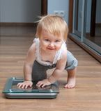 Cute baby on home scales Stock Image