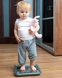 Cute baby on home scales. Cute baby with a toy check own weight on home scales Stock Images