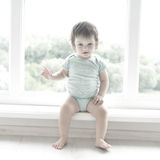 Cute baby at home in white room is sitting near window. The beautiful baby could be a boy or girl and is wearing body suit. Stock Images
