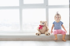 Cute baby at home in white room is sitting near window. The beautiful baby girl with teddy bear. Royalty Free Stock Images