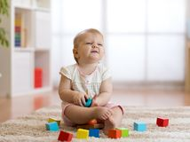 Cute baby girl playing with toys in living room stock image