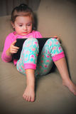 Cute Baby on iPad. A cute little 3 year old baby girl in her pajamas working on an iPad while laying on the couch. Shallow depth of field stock images