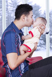 Cute baby kissed by his dad at home Stock Photography