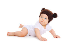 Cute baby in knitted brown hat with ears bears crawls on white Stock Photography