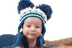 Cute baby in knitted hat with big pom-pons Stock Images