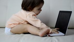 Cute baby with laptop computer on the white blanket background stock video