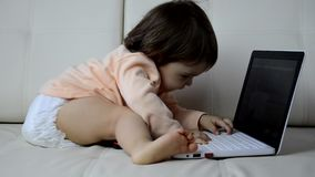Cute baby with laptop computer on the white blanket background stock video footage