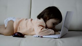 Cute baby with laptop computer on the white blanket background stock footage