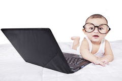 Cute baby with laptop and glasses on bed Royalty Free Stock Photo