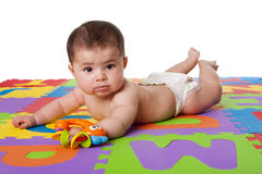 Cute baby laying on belly. Beautiful cute happy playful Caucasian Hispanic baby laying on belly on a colorful padded floor tiles with alphabet letters and a toy Stock Photos