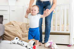 Cute baby learning how to walk with mother at home Royalty Free Stock Images
