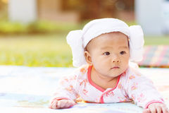 Cute  baby lie prone on ground at park. Cute Asian baby lie prone on ground at park Stock Photos