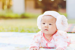 Cute  baby lie prone on ground at park. Cute Asian baby lie prone on ground at park Royalty Free Stock Photos