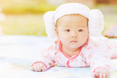 Cute  baby lie prone on ground at park. Cute Asian baby lie prone on ground at park Stock Images