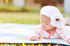 Cute  baby lie prone on ground at park. Cute Asian baby lie prone on ground at park Royalty Free Stock Photo