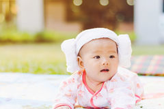 Cute  baby lie prone on ground at park. Cute Asian baby lie prone on ground at park Royalty Free Stock Image