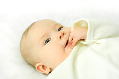 Cute baby lies on the bed and sucks his fingers Royalty Free Stock Image